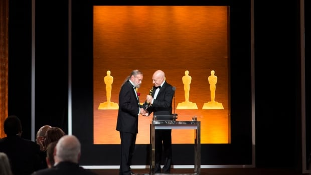 Actor Patrick Stewart gives the Oscar to visual effects technologist Jonathan Erland, recipient of the Gordon E. Sawyer Award during the Academy of Motion Picture Arts and Sciences' Scientific and Technical Awards Ceremony Saturday in Beverly Hills, Calif.