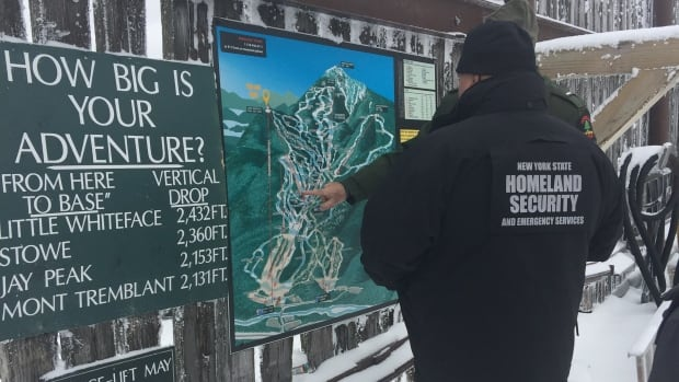 A member of New York State Homeland Security and Emergency Services stands in front of a map of Whiteface Mountain on Sunday.