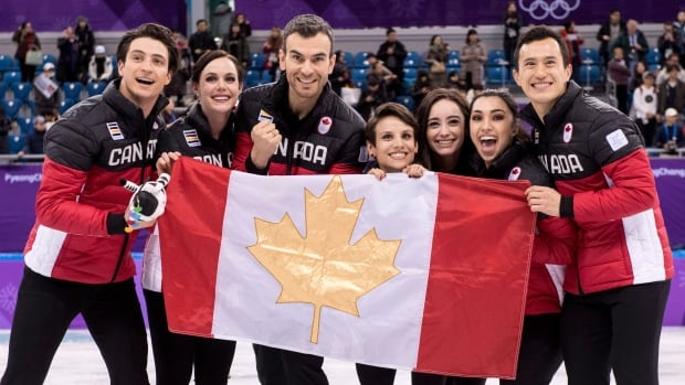 Canada's Scott Moir, left to right, Tessa Virtue, Eric Radford, Meagan Duhamel, Kaetlyn Osmond, Gabrielle Daleman, and Patrick Chan celebrate their gold medal victory in the team figure skating event.