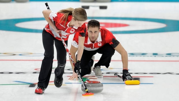 Canada's Kaitlyn Lawes, left, sweeps as John Morris shouts instructions during a mixed doubles match at the Olympics.