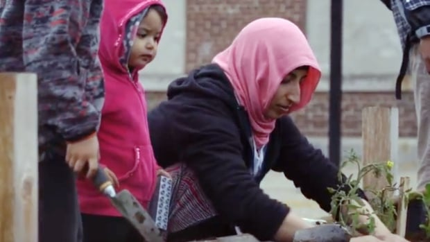 Families tend gardens at Lord Selkirk Park in this image from the documentary A Good Place to Live.