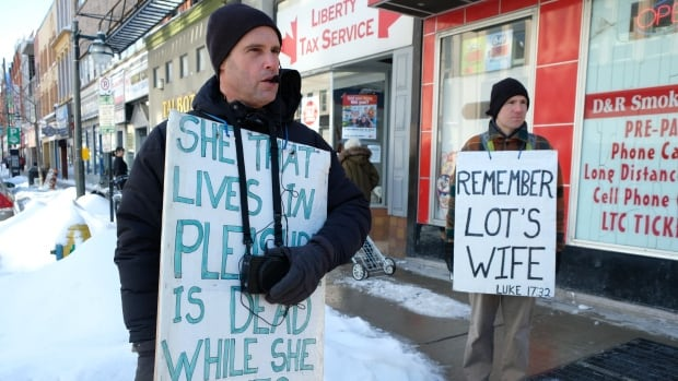 Steven Ravbar, left, and Matthew Carapella were back in their usual spot at the corner of Richmond and Dundas in London, Ont., on Monday.
