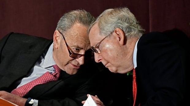 Senate Minority Leader Charles Schumer leans in to speak to Senate Majority Leader Mitch McConnell before his speech at the McConnell Center's Distinguished Speaker Series Monday in Louisville, Ky.