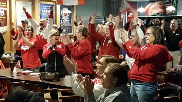 The crowd at St. Vital Curling Club stands and cheers after Kaitlyn Lawes and John Morris win mixed doubles curling gold on Tuesday morning.