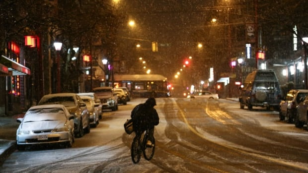 A man rides his bike through Vancouver's Chinatown as snow begins to stick to the roads.
