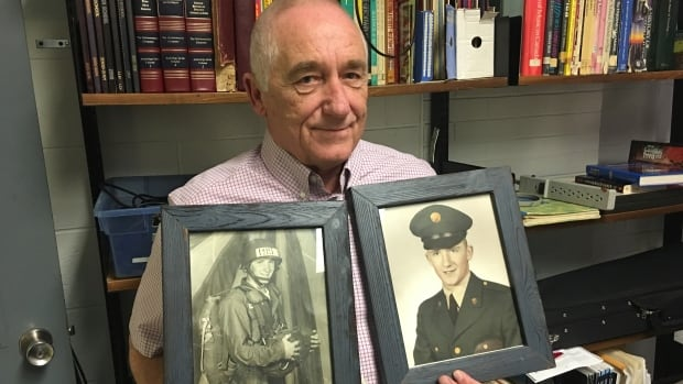 Wayne Hillman holds two photos of himself from the Vietnam War, which had been lost for ten years.