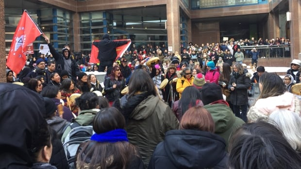 A crowd gathers to hold a strawberry ceremony to honour MMIWG on Valentine's Day in front of Toronto Police Headquarters. Feb. 14, 2018