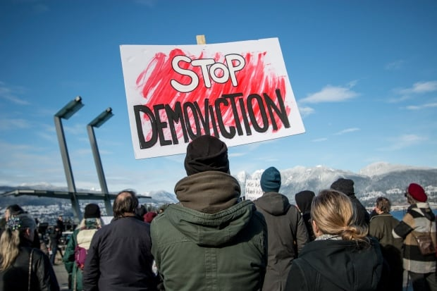 Stop demoviction sign holder, Vancouver housing rally 18 Feb 2018