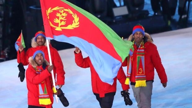 Flag bearer Shannon-Ogbani Abeda of Eritrea leads the team during the Opening Ceremony of the PyeongChang 2018 Winter Olympic Games, as his family watched from the stands.