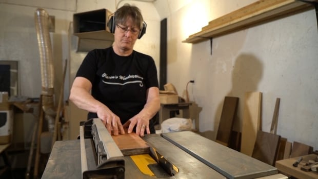 Karen Thorp prepares a piece of exotic wood for use in a woodworking project.