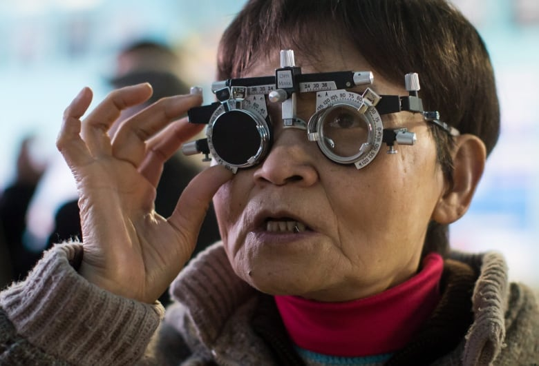 a86cb6607148 Bao Qin Song reads the letters on an eye chart while being examined on  Sunday. She says it s been five years since she had her prescription  checked.