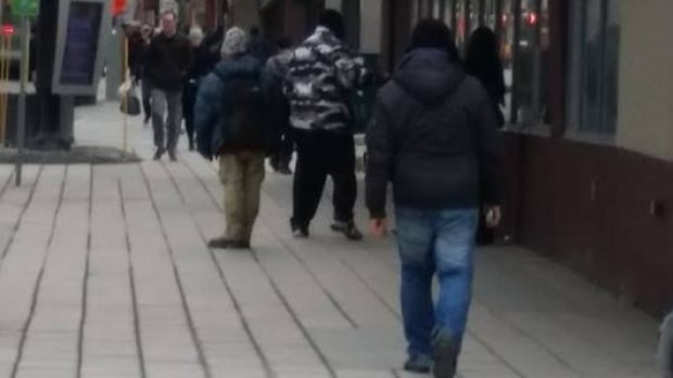 Stephanie McLeod took this photo of the man in the blue jeans and black jacket she said kicked her on Rideau Street earlier this week.