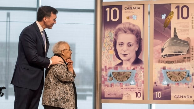Wanda Robson, right, sister of Viola Desmond, admires a $10 banknote while standing alongside Finance Minister Bill Morneau. The new bill featuring the civil rights icon's image was unveiled in Halifax on Thursday.