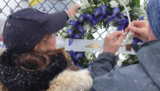 Lori Chynn hangs a memorial wreath