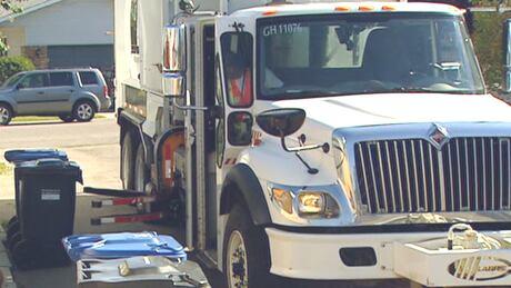 Black bin garbage pickup truck Calgary