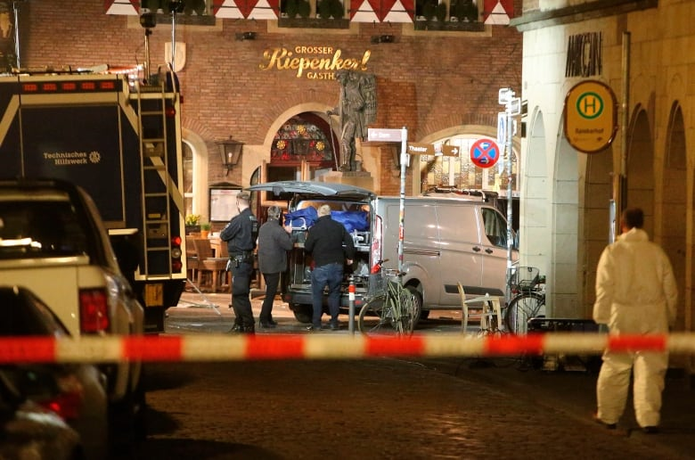 418b0c7f7f A body is loaded into a vehicle in front of a restaurant in Muenster early  Sunday. (David Young dpa via AP)