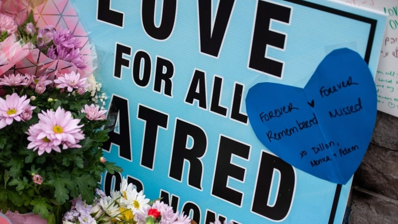 People leave signs, cards and flowers at a memorial on Yonge Street on  Tuesday. (Galit Rodan/Canadian Press)