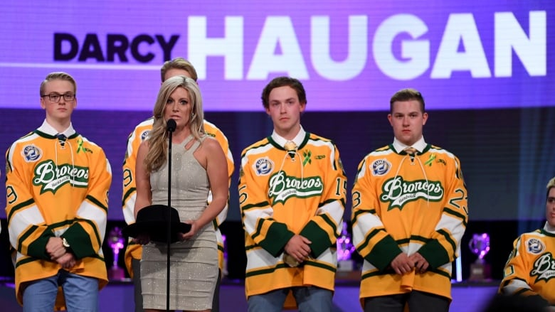 18455c0fb Christina Haugan and surviving members of the Humboldt Broncos accept the  Willie O Ree Community Hero Award for her late husband Darcy
