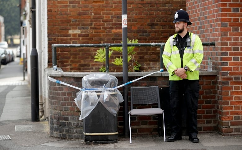 A British police officer guards a cordon around a plastic-covered rubbish bin in Salisbury, England, on Thursday, as investigators seek clues into how the two Britons were exposed to a military-grade nerve agent.(Matt Dunham/Associated Press)