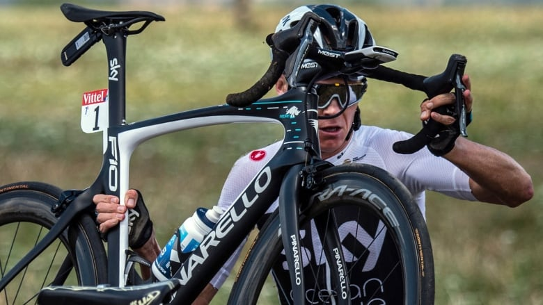 2300e3a82 Britain s Chris Froome carries his bicycle after falling into a ditch when  crashing with other rider during the first stage of the Tour de France  cycling on ...