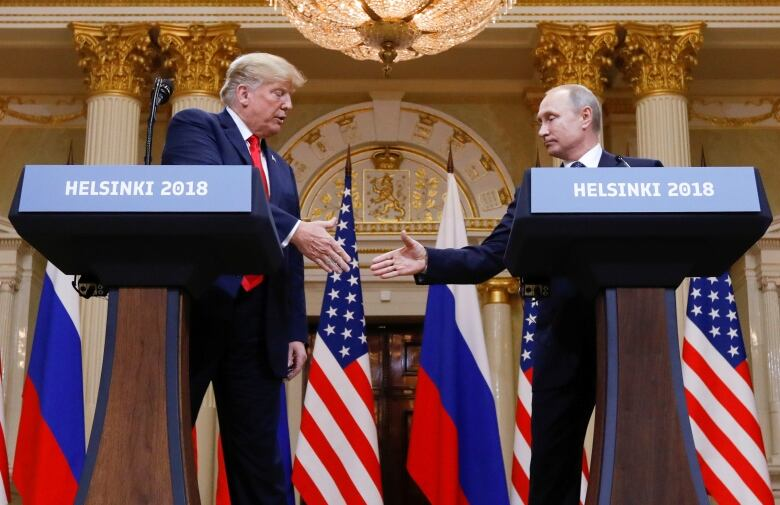 U.S. President Donald Trump and Russia's President Vladimir Putin shake hands during a joint news conference after their meeting in Helsinki, Finland, on Sunday. (Kevin Lamarque/Reuters)