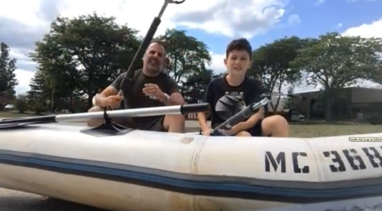 Mark and Tom Nardone sit inside their boat with the custom made trash  grabbers. (Chris Ensing/CBC)
