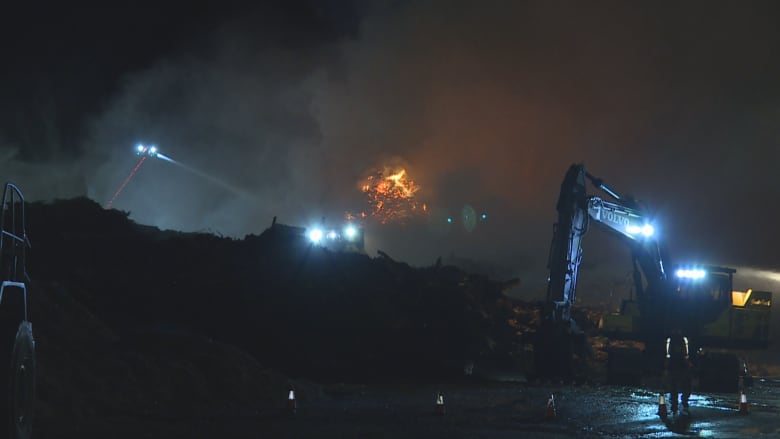 Fire crews douse debris in water as excavators move wood away from the  fire. (Cory Correia/CBC News)