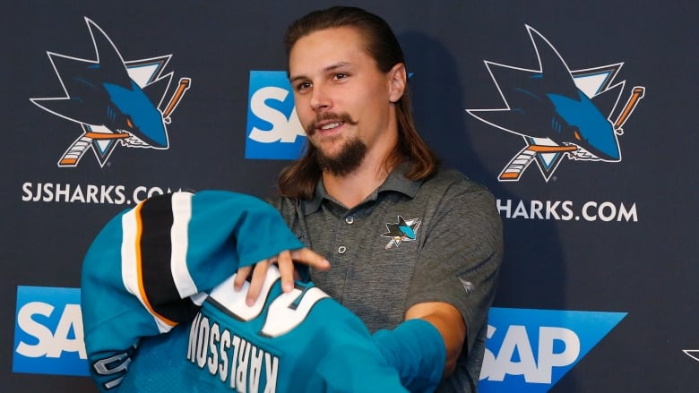 99f429b193c Erik Karlsson tries on his Sharks jersey at his introduction on Wednesday.  (Josie Lepe/Associated Press)