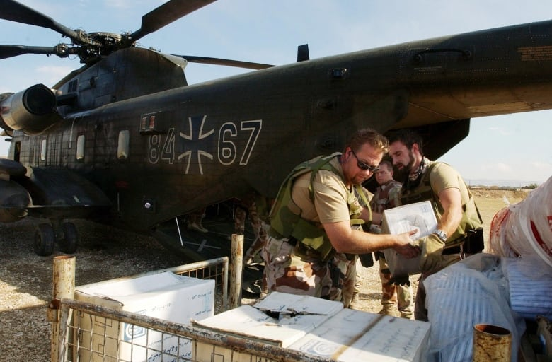 Norwegian soldiers that were part of the International Security Assistance Force load humanitarian aid onto a German helicopter in Afghanistan in 2006. Norway is the world's most generous foreign-aid donor.(Musadeq Sadq/AFP/Getty Images)