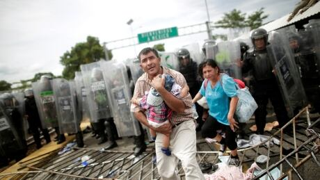 Migrants break Guatemala border fence, met by Mexican police
