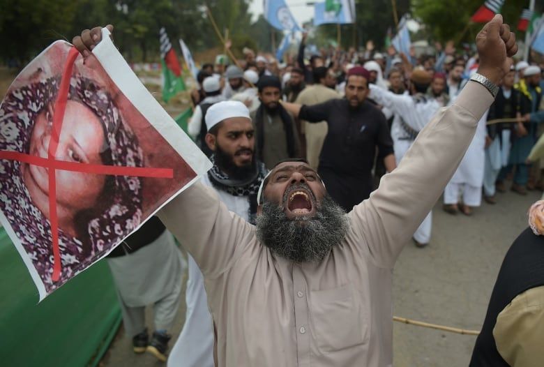 A Pakistani supporter of the Ahle Sunnat Wal Jamaat (ASWJ), a hardline religious party, holds an image of Bibi during a protest rally following the Supreme Court's decision to overturn Bibi's conviction for blasphemy, in Islamabad, on Nov. 2, 2018. (Aamir Qureshi/AFP/Getty Images)