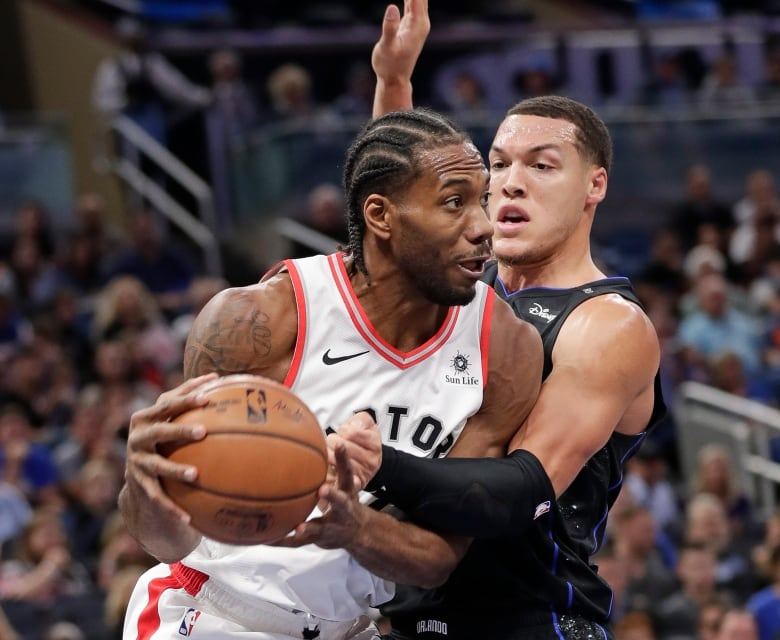 Toronto Raptors Kawhi Leonard, left, makes a move to get around Orlando  Magics Aaron Gordon during the first half. Leonard led Toronto with 18  points on ...
