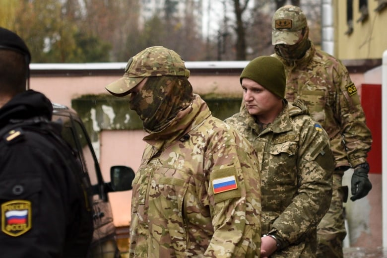 A Ukrainian sailor, second right, is escorted by Russian intelligence agency FSB officers from a court in Simferopol, Crimea, Wednesday, Nov. 28, 2018. Ukraine released what it said was the exact location where its ships were fired on Sunday by Russia, showing that they were in international waters approaching Kerch Strait from the west, not from the east, as Russian President Vladimir Putin has suggested.(The Associated Press)