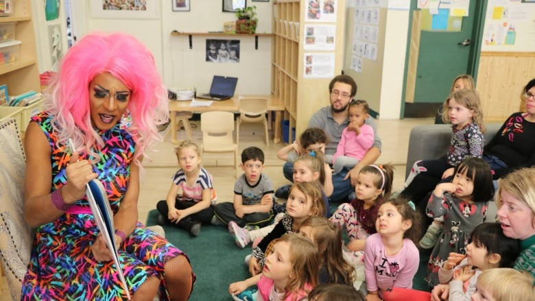 Barbada (Sébastien Potvin) reads to children at Over The Rainbow daycare's first drag queen story time event. (Shari Okeke/CBC)