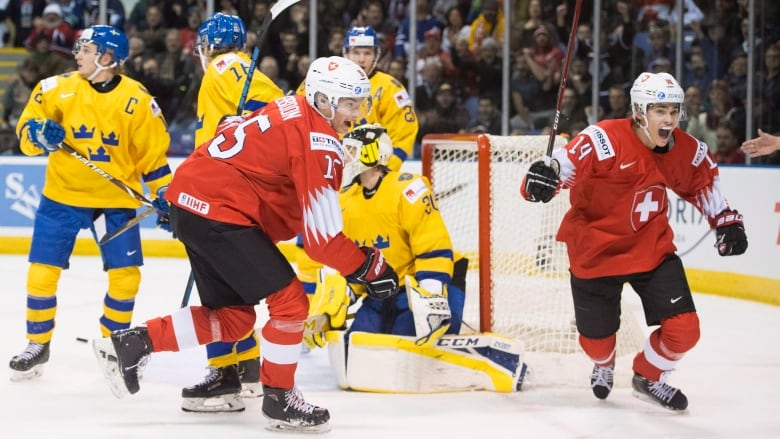 6f9a28c8cdf Switzerland s Sandro Schmid and Matthew Verboon celebrate their team s  second goal in an upset win over Sweden in the quarter-finals of the world  junior ...