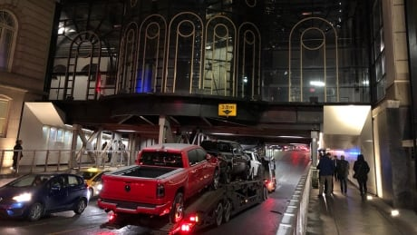 Cars crushed as trailer gets stuck under downtown Calgary bridge