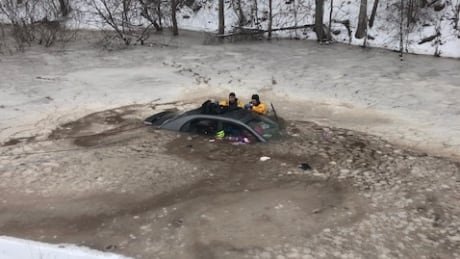 Firefighters check Ahsley Holland's submerged car