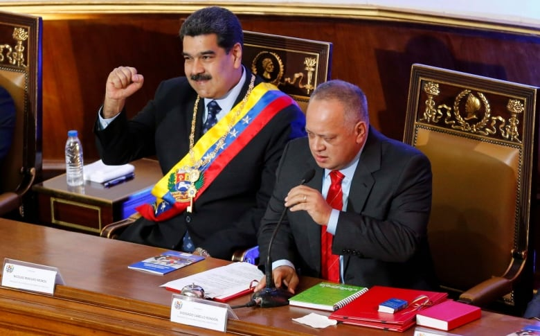 Venezuela's President Nicolas Maduro holds up his fist to greet members of the Constitutional Assembly next to Assembly President Diosdado Cabello who starts a special session for Maduro's annual address to the nation, inside the National Assembly in Caracas on Jan. 14. Maduro blames Venezuela's crisis on an 'economic war' waged by the local elite and the U.S. (Ariana Cubillos/Associated Press)