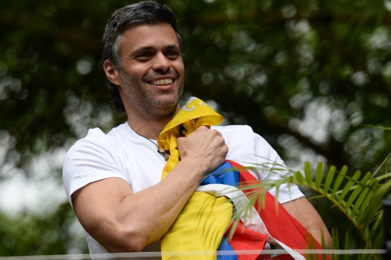 Venezuelan opposition leader Leopoldo Lopez holds a national flag as he greets supporters outside his house in Caracas after he was released from prison and placed under house arrest for health reasons on July 8, 2017.(Federico Parra/AFP/Getty Images)