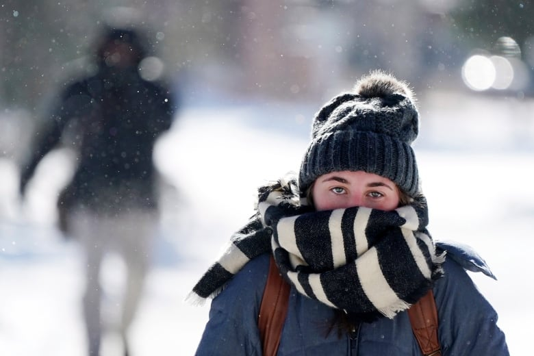 Jillian Hansen, a student at the University of Minnesota, walks on campus wrapped up in an oversized scarf amid snowflurries Tuesday. At least four deaths have been tied to the cold snap in the U.S. (Anthony Souffle/Star Tribune via AP)