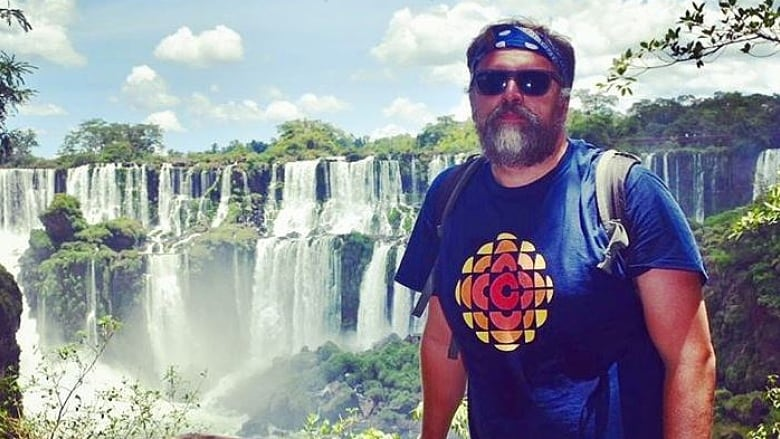 Why this man poses in a CBC T-shirt as he globe-trots from