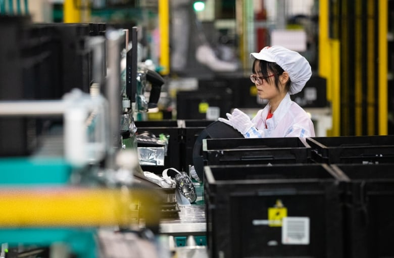A worker oversees automated production at the Huawei plant in Dongguan. (Saša Petricic/CBC)