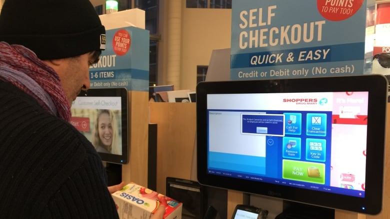 c8bce87edbed A customer uses the self-checkout at a Shoppers Drug Mart. (CBC)