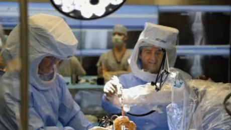 Dr. Anthony Adili with robot arm