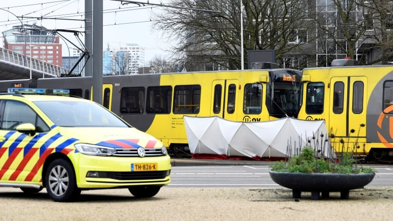 b4d781e891863a A barrier erected by police obscures the victims of a deadly tram shooting  in the Dutch city of Utrecht this morning. (Piroschka van de Wouw Reuters)