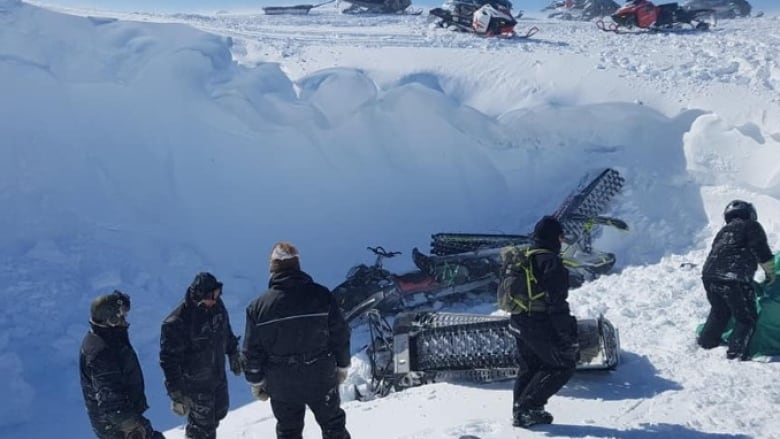 Snowmobilers airlifted after crashing into snow crater