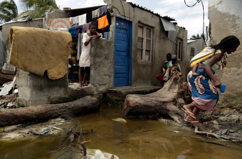 A woman carrying a baby on her back jumps as she tries to avoid stepping on the dirty water in Beira Wednesday. Cyclone-ravaged Mozambique faces a 'second disaster' from cholera and other diseases, the World Health Organization is warning. (Themba Hadebe/Associated Press)