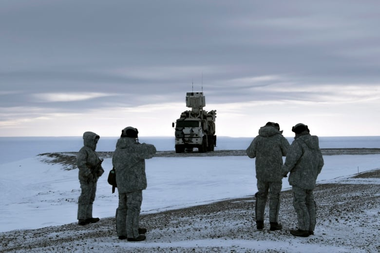 Russian solders stand as Pansyr-S1 air defense system is seen in the background on the Kotelny Island. Russia has made reaffirming its military presence in the Arctic the top priority amid an intensifying international rivalry over the region that is believed to hold up to one-quarter of the planet's undiscovered oil and gas.(AP Photo/Vladimir Isachenkov)