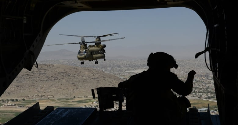 A U.S. soldier, part of the NATO-led International Security Assistance Force (ISAF), mans a machine gun aboard a Chinook helicopter over the Gardez district of Paktia province in August 2014.(Shah Marai/AFP/Getty Images)