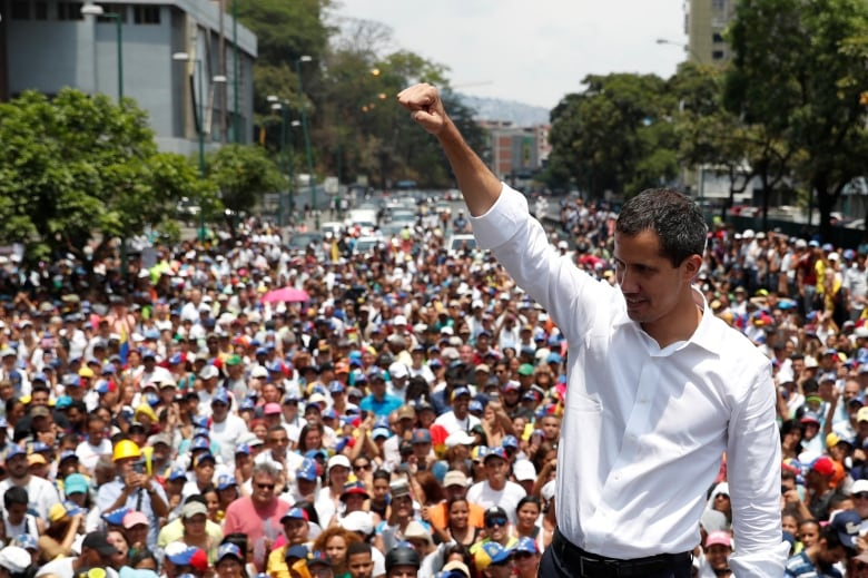 Guaido gestures as he speaks to supporters during a rally against Maduro's government and to commemorate May Day in Caracas Wednesday. (Carlos Garcia Rawlins/Reuters)